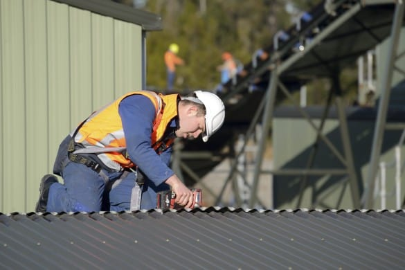 Greymouth, New Zealand, June 22, 2015: A builder wears a safety harness while working at heights on a roof during demotion of infrastructure at the Pike River Coal Mine near Greymouth, New Zealand.The mine has been closed since efforts failed to recover the bodies of 29 miners lost in an explosion in 2010.
