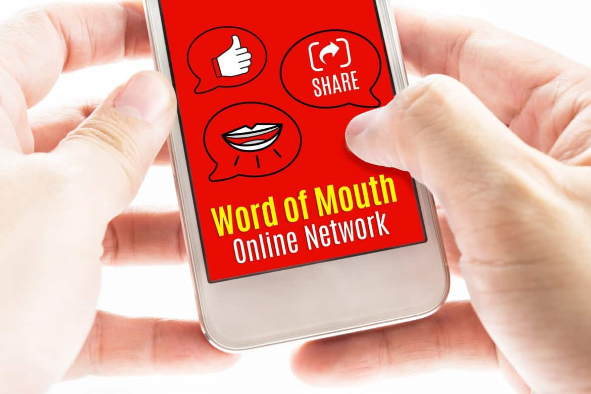 Two hand holding smart phone with word of mouth online